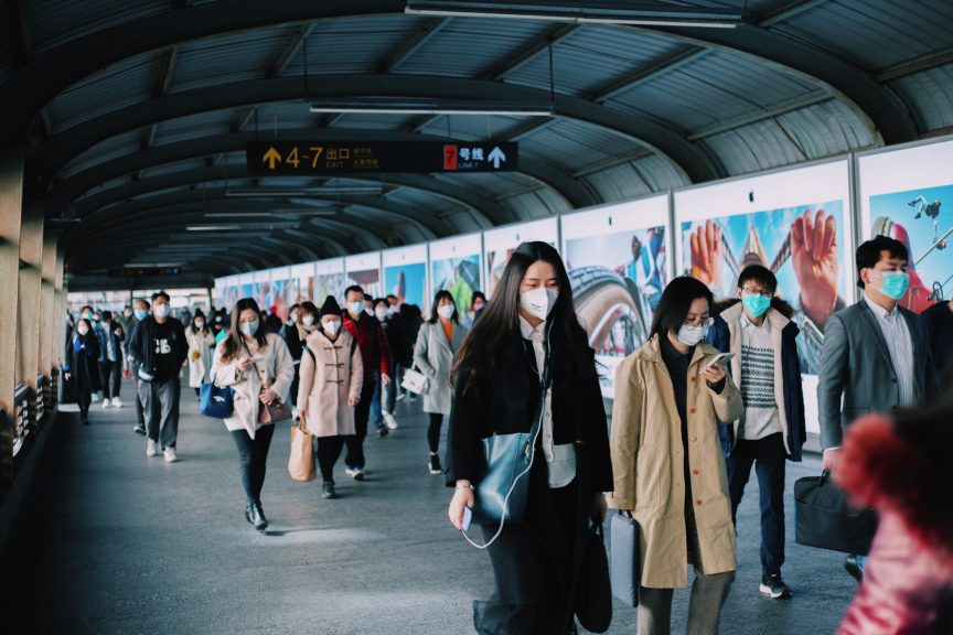 People at the train station with mandatory mask